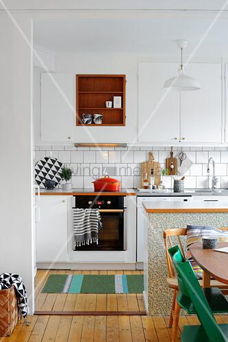 Blick in die offene Küche mit weißen Fronten und Dielenboden