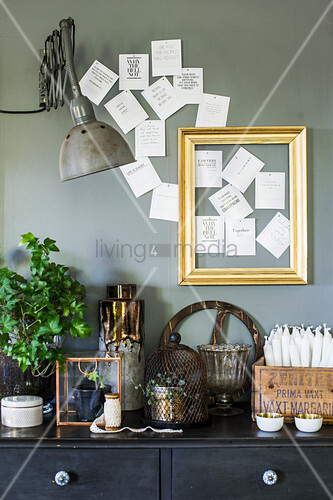 Vintage ornaments on black chest of drawers against grey wall