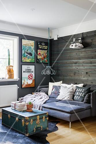Schlafsofa mit Kissen vor Holzwand und Koffer als Couchtisch