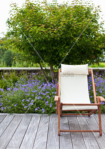 Deck chair on terrace in front of bed of cranesbill geraniums and small tree