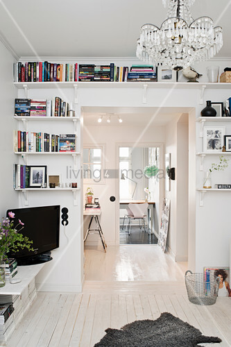 Bookshelves surrounding an open doorway leading into living room