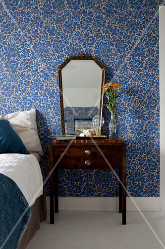 Old mirror and bedside table against blue floral wallpaper