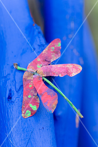 Dragonfly made from painted sycamore seeds on blue branch
