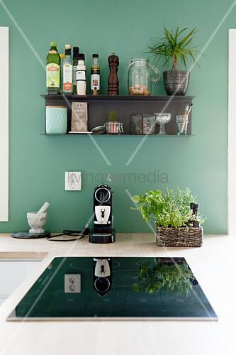 Black shelf mounted on petrol-blue kitchen wall above hob