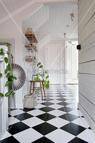 Bright hallway with white wood-panelled walls and chequered floor
