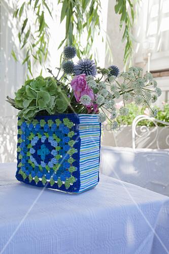 Blumen in einer Vase mit blau-grün gehäkelter Hülle