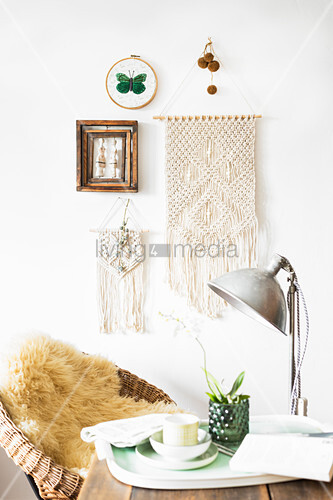 Macrame wall hanging on white wall with cup and flowers on tray in foreground