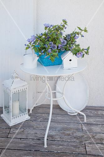 Blaue Blumen im Korb auf dem Metalltisch mit weißer Deko