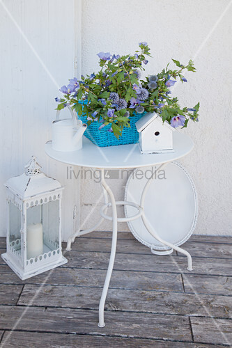 Blue-flowering plants in basket on metal table and white ornaments