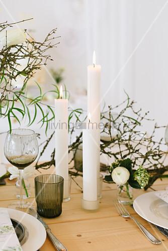 Gedeckter Hochzeitstisch mit Frühlingsblumen, trockenen Zweigen und Cylinderkerze