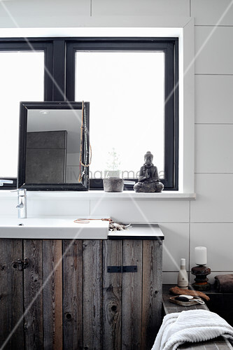 Rustic washstand made from wooden boards below window, Buddha figurine and mirror on windowsill in bathroom