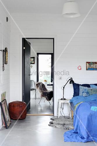 Vintage Hocker als Nachttisch neben Bett mit blauer Bettwäsche im Schlafzimmer
