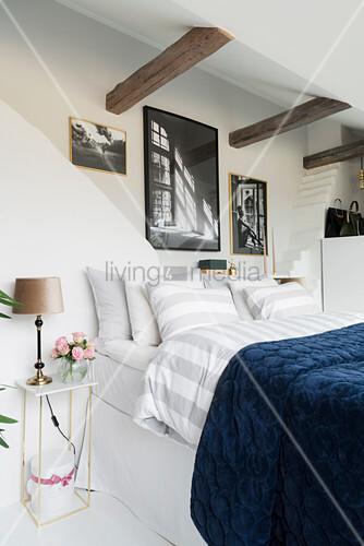 Double bed below rustic wooden beams in white bedroom