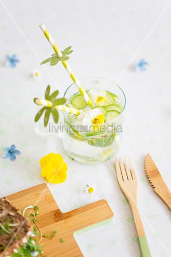 Gurkenwasser mit essbaren Hornveilchen und Strohhalm mit kleiner Papierdeko