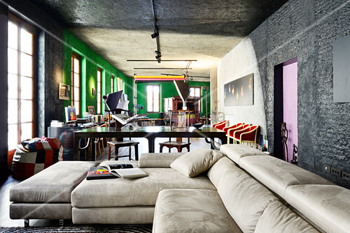 Pale leather couch in renovated loft apartment with black and green walls