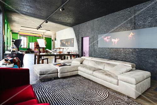 Helle Ledercouch, darüber moderne Kunst an schwarzer Wand in renoviertem Loft