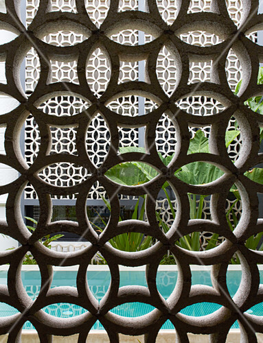 Half-open wall of ornamental perforated bricks next to pool