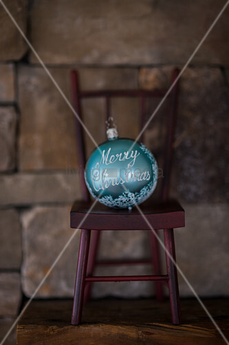 Turquoise Christmas bauble on miniature chair