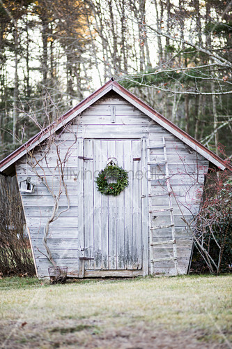 Wooden garden shed decorated with Christmas wreath