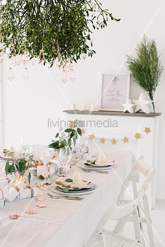 Modern place settings on white Christmas table below bunch of mistletoe