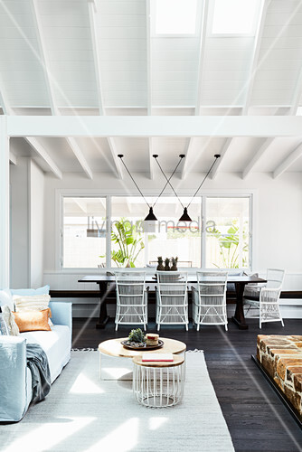 Lounge area and dark dining table with white rattan chairs in open-plan interior