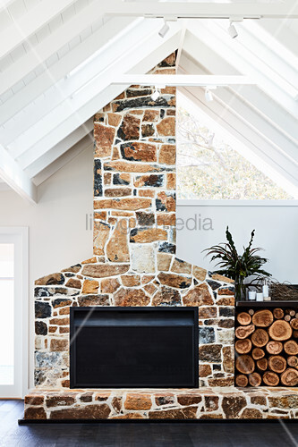 Firewood stacked next to fireplace with stone surround and chimney breast