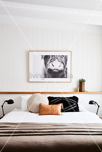 Scatter cushions on double bed in bedroom with white wood-panelled walls
