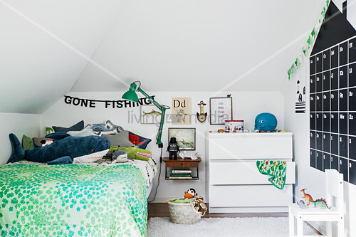 House-shaped calendar on wall in child's bedroom with green accents