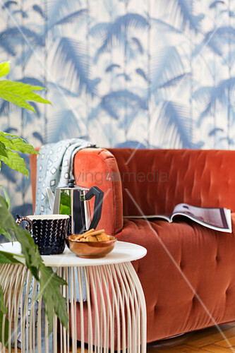 Coffee cup on delicate side table next to velvet armchair