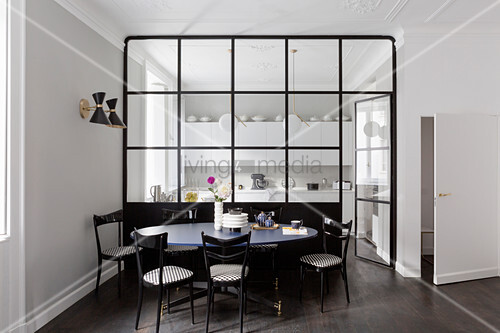 Black chairs around dining table in front of glass partition wall looking into kitchen