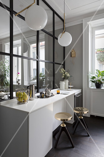Gilt stools at kitchen counter against glass and steel partition wall