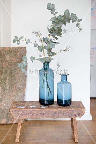 Zwei blaue Vasen mit Eukalyptuszweigen auf einem Schemel
