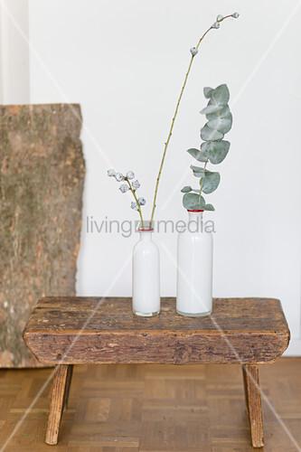 Two white vases with eucalyptus twigs on stool