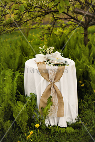 Table festively set for afternoon coffee in garden