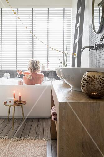 Waschtisch mit zwei Aufsatzbecken im Bad mit weihnachtlicher Deko, Frau in der Badewanne