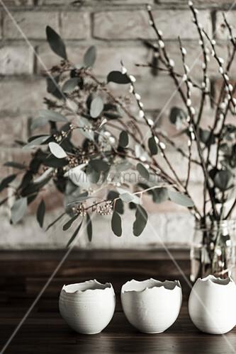 Keramikeier, Eukalyptuszweige und Palmkätzchen als Osterdeko