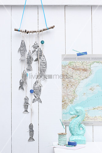 Mobile of hand-made metal fish hung on board wall