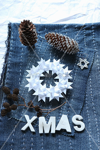 Wreath of folded paper stars on denim embroidered with lines