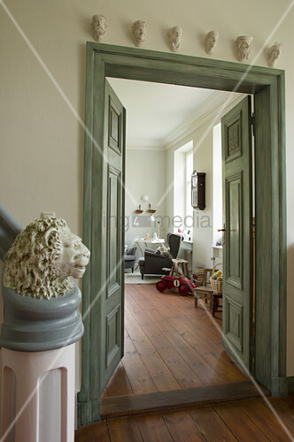 Newel post topped with lion head and green-painted double doors in country house