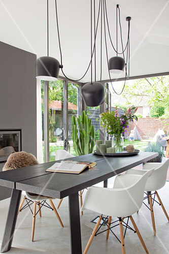 Wooden dining table and white shell chairs below pendant lamps