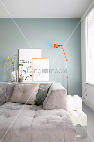 Modern grey sofa in front of pale blue wall in living room