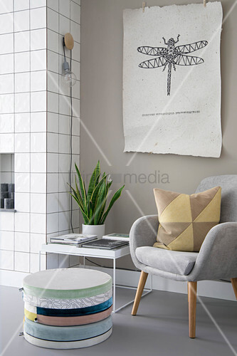 Stacked floor cushions and armchair below picture of dragonfly on wall
