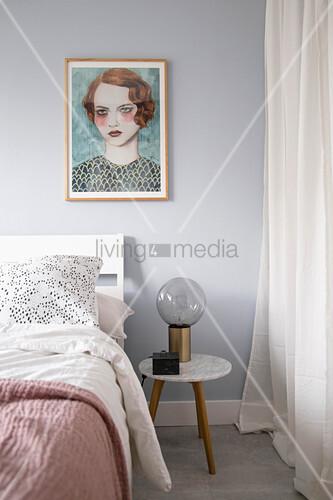 Gemälde einer Frau über dem Bett im femininen Schlafzimmer