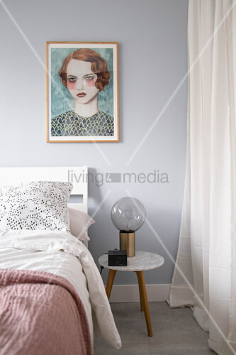 Portrait of woman above bed in feminine bedroom
