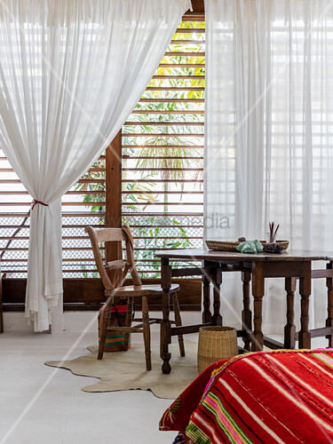 View across bed to wooden table in front of windows with louvre blinds