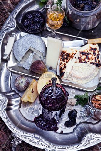 Verschiedene Käsesorten, Marmelade und Früchte auf Vintage Silbertablett