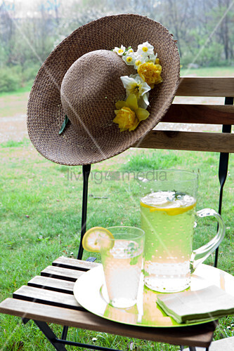 Jug and glass of lemonade and summer hat decorated with flowers on garden chair