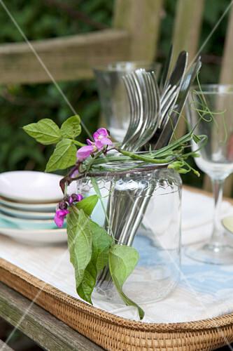 Erbsenranke um Glas mit Besteck geschlungen