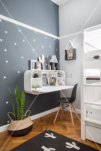 Wall-mounted shelving unit with integrated fold-down desk in child's bedroom