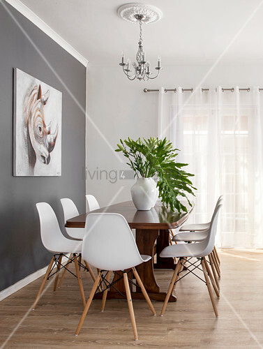 White designer chairs around wooden table next to grey accent wall